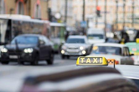 Photo pour Taxi dans les rues de la ville sur un fond indistinct d'autres voitures et véhicules - image libre de droit