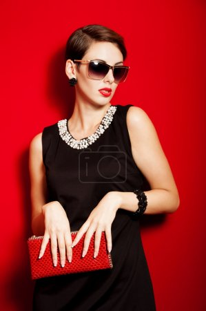 Beautiful girl with a red clutch bag in her hands and sunglasses