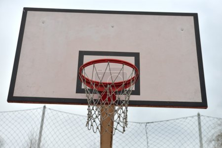 Basketball board under cloudy sky in a school yard. Concept of k