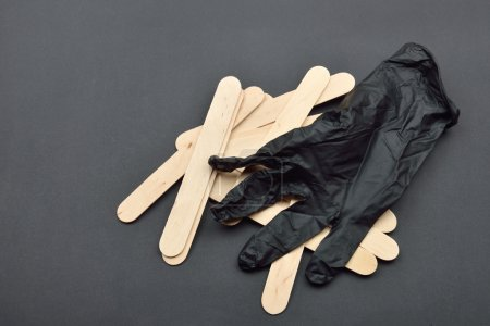 Black glove and wooden spatulas for wax on black. Preparing for