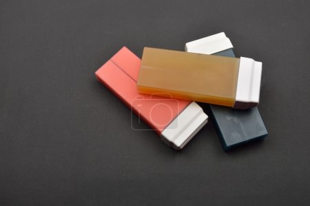 Picture of liposoluble wax cartridges for waxing on black backgr