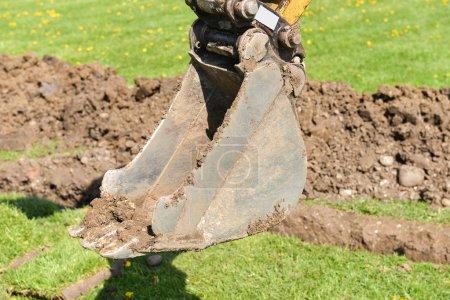 Photo pour Excavatrice bras creusant profondément, travaux sur un chantier de construction - image libre de droit