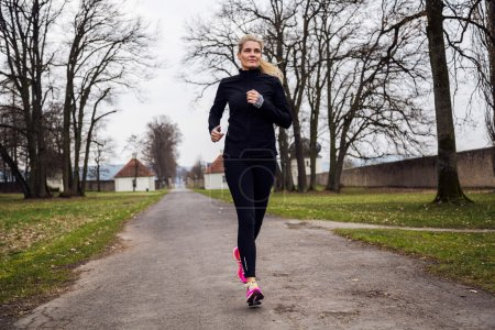 Photo for Attractive middle aged woman doing sport in the park. Female runner exercising - Royalty Free Image