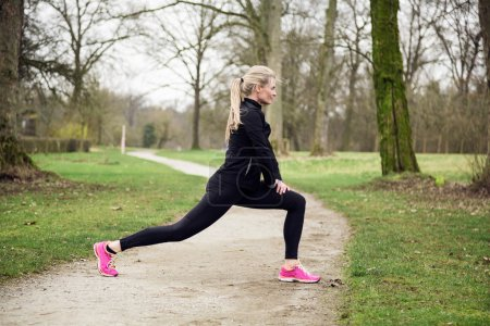 woman stretching her legs in the park