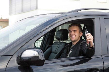 Photo pour Heureux jeune adulte tenant des clés de voiture dans sa main et célébrant son nouveau permis . - image libre de droit