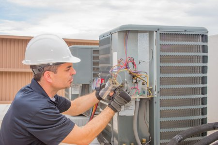 Photo pour HVAC technician working on a capacitor part for condensing unit. - image libre de droit