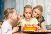 Matka a dvě děti pečení nalijte hmoty do formy na muffiny připravovali Velikonoce