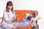 Pediatrician check temperature on thermometer little girl