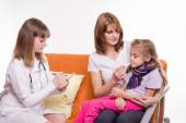 Doctor writes a prescription for sick girl who sits at mum on hands