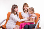 Pediatrician checks breath stethoscope a little girl in the arms of mother