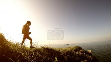 Photo for Young woman hiker hiking on sunrise mountain peak - Royalty Free Image