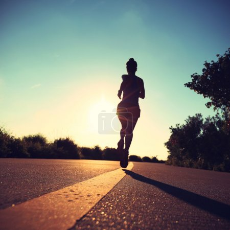 Photo for Young fitness woman running on sunrise seaside road - Royalty Free Image
