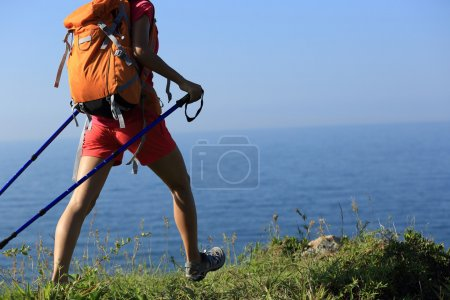 woman backpacker on seaside mountain