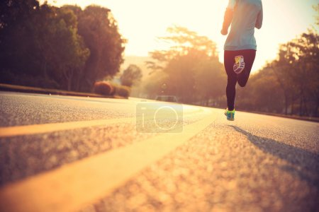 Photo for Young fitness woman running at road - Royalty Free Image