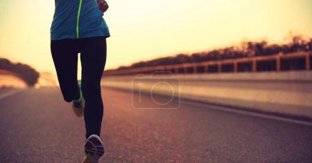 woman running on sunrise road