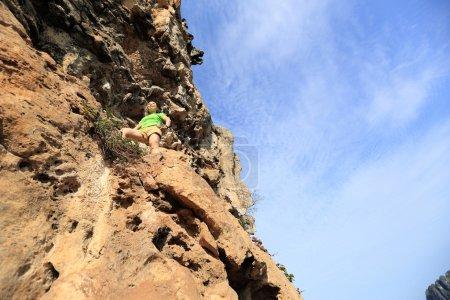 woman rock climber at  mountain cliff