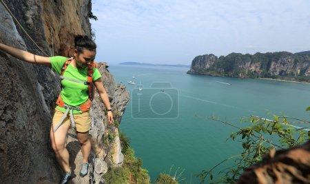Foto de Mujer joven escalador escalada en el acantilado de la montaña junto al mar - Imagen libre de derechos