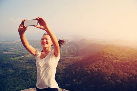 woman taking photo at mountain