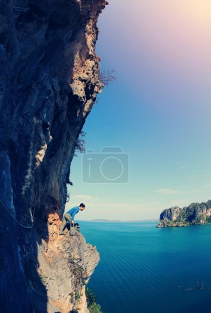 Foto de Mujer joven escalador de rocas en acantilado de montaña junto al mar - Imagen libre de derechos