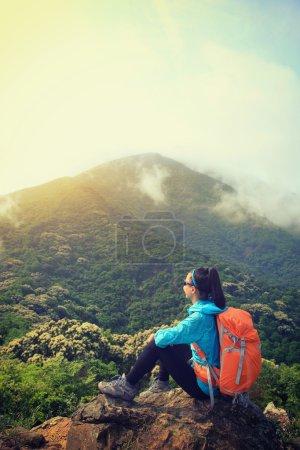Photo pour Jeune femme avec randonneurs routards au sommet de la forêt - image libre de droit