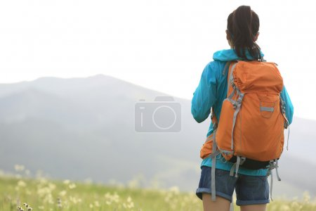 woman hiker walking on trail in grassland