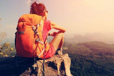 backpacker sitting on mountain peak