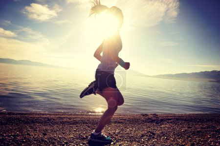 Photo for Healthy lifestyle young fitness woman runner running on road at sunrise seaside - Royalty Free Image