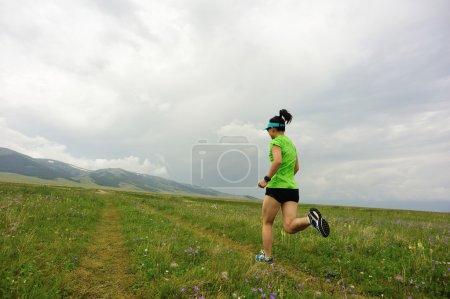 trail runner running on peak