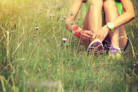 Photo for Young woman runner tying shoelace on nature trail - Royalty Free Image