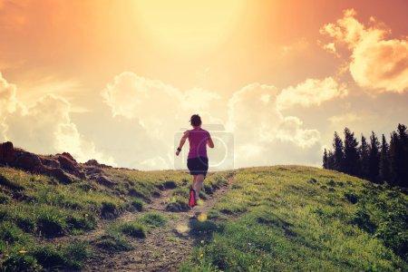 woman running on beautiful mountain peak