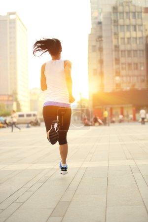 Runner athlete running on city street.