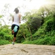 Young fitness woman running at forest trail...