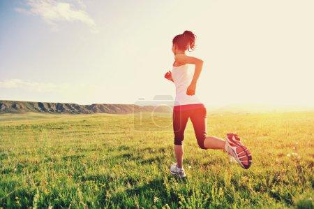 Runner athlet running on grass seaside.