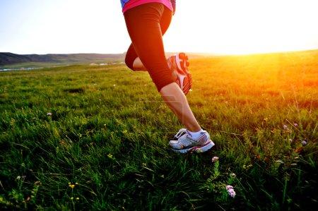 Runner athlete legs running on grass seaside