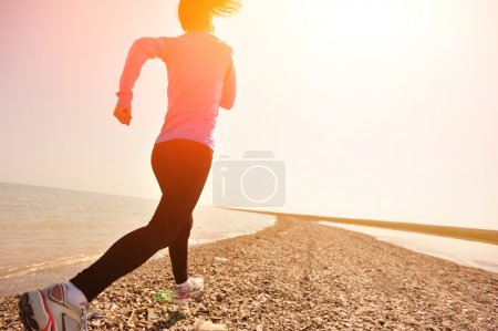 Photo for Runner athlete running on stone beach of qinghai lake. woman fitness jogging workout wellness concept. - Royalty Free Image