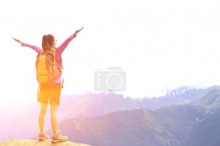 Cheering hiking woman open arms on mountain peak of tibet,china