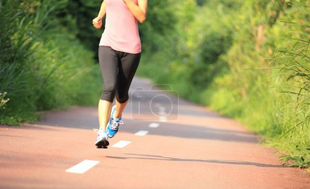 Oung fitness woman legs running at forest trail