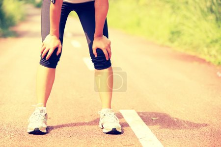 Photo for Tired woman runner taking a rest after running hard in countryside road. sweaty athlete after marathon training in country road. - Royalty Free Image