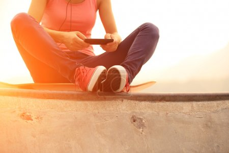 Woman skateboarder listening music from