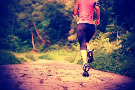 Woman running at forest trail