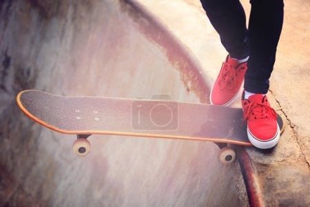 Skateboarding woman legs at sunrise