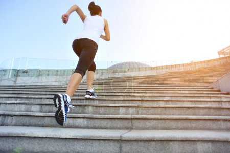 Photo for Runner athlete running on stairs. woman fitness jogging workout wellness concept. - Royalty Free Image