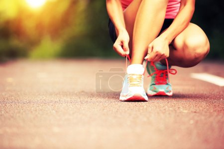Photo for Young woman runner tying shoelaces - Royalty Free Image