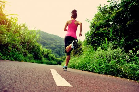Photo for Young fitness woman running at forest trail in summer day - Royalty Free Image