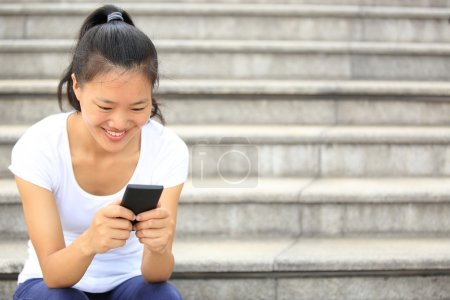 Beautiful young asian woman using smart phone