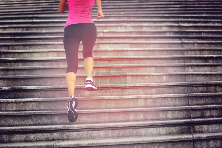 Photo for Sports woman legs running up on stone stairs - Royalty Free Image