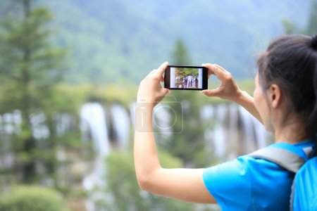 Woman tourist taking photo with smart phone...
