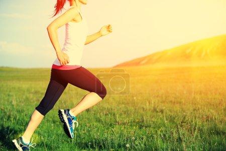 Runner athlete running on grass seaside. woman fitness sunrise or sunset jogging workout wellness concept.