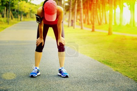 Photo for Tired woman runner taking a rest after running hard in tropical park trail - Royalty Free Image