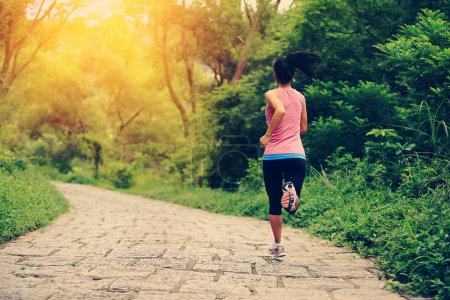 Young fitness asian woman running at forest trail